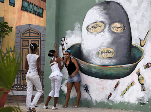 A girl takes a photograph with a mobile phone in a square adorned by murals in Havana